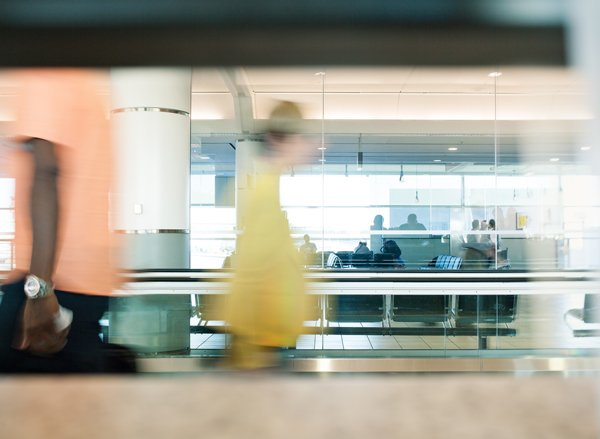 Man walks across moving walkway in airport
