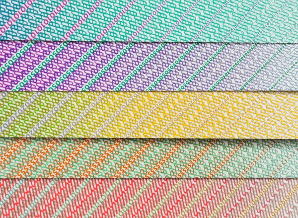 Extreme close up image of different coloured currency layered to create a rainbow effect