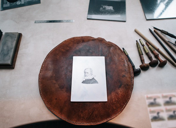 Table with old fashioned etching tools and leather disk with a picture of historical figure on it