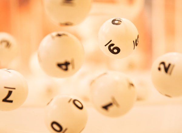 White, numbered lottery balls suspended in motion
